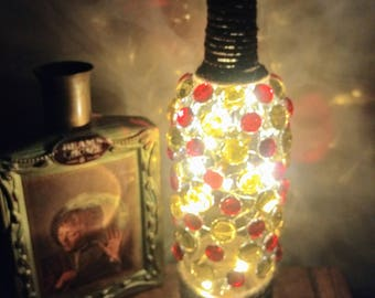 Recycled Wine Bottle. Bottle with lights decorated with Red and Gold Glass Stones. Fairy Lights inside a bottle