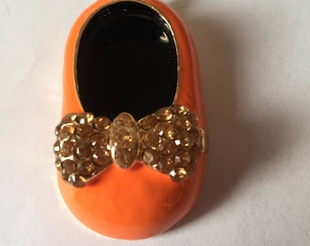shoe: enamel orange and adorned with a rhinestone bow