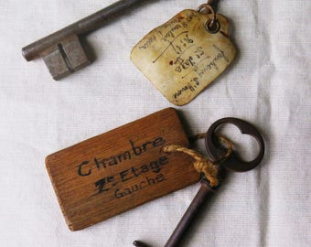 Two antique hotel keys with name tags