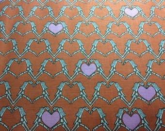 Riley Blake Zombie Love fabric. Orange background with skellington arms holding a pink heart