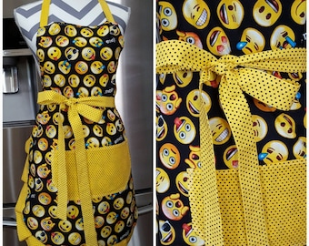 Adult apron. Woman's apron. Emoji faces of all kinds. Yellow with black polka dots on pocket, ties and frills.