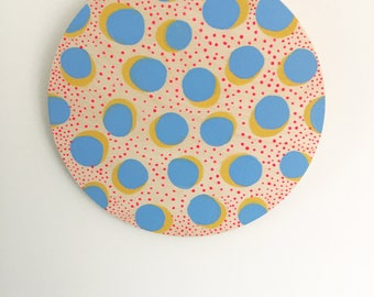 Pop art inspired painted pattern on plywood circle