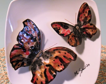 Composition consisting of two butterflies hand-made ceramic and decorated, served on a China plate. 20 x 20 cm.