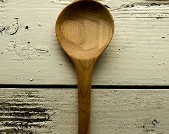 Wooden cook's and baker's spoon handmade in light to darker grained yellow birch with large round bowl and long sturdy handle
