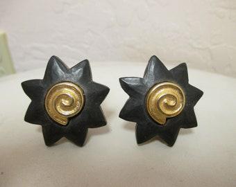 Givenchy Black Bakelite Sunburst clip earrings with a Gold tone shell center