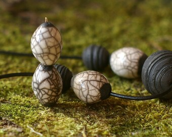 raku ceramic beads, setot of 2 beads in the shape of small olive - beautiful bright white on black clay, artisan handmade raku beads,