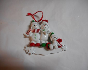 Family of 3 snowmanon sled