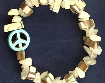 Green metallic and prehnite beaded bracelet with a turquoise peace sign charm