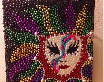 Mardi Gras Bead Art Mask Surrounded by Feathers