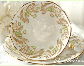 Queen Anne, England: Tea cup and saucer with gold gilding and green flowers