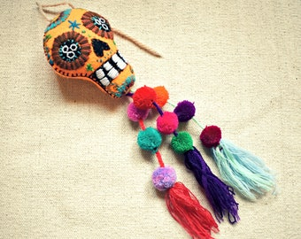 Embroidered skull, day of the dead. Orange color with tassel pompoms. Decoration