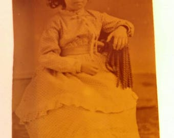 Antique Tintype Young Girl Sitting in a Chair Wearing Long Beautiful Dress.