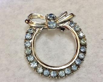 Light blue rhinestone rhodium metal circle brooch pin.
