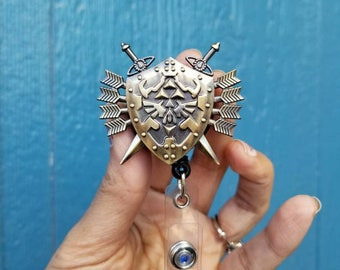 The Legend of Zelda Hylian shield badge reel clip. Zelda retractable badge id holder. Comes with reel. BadgeBlingCS. Bronze. Triforce