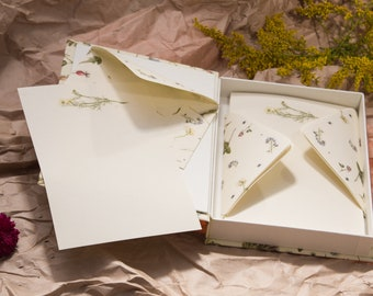 Stationery set in a cardboard box, a set of envelopes and paper, letters, herbs, flowers