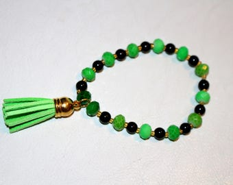 A Cute Green and Black Beaded Stretch Bracelet with a Green Tassel