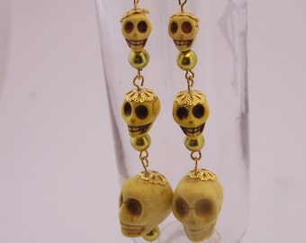 Earrings on hooks made of skulls yellow of different sizes