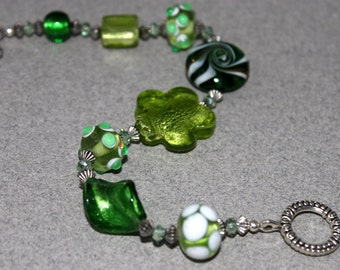Handmade beaded bracelet of big lampworked and foil glass beads in tones of green make for FUN