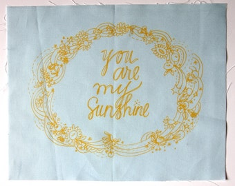embroidery pattern on fabric You Are My Sunshine yellow on blue