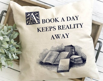 """Bookish Gifts, canvas cushion cover hand-printed with the quote """"a book a day keeps reality away"""""""