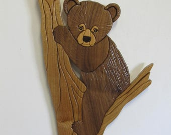 Intarsia baby bear cub in tree