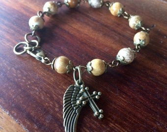 Handmade bracelet with semi-precious jasper beads with cross and wing charm in antique bronze
