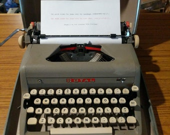 1957 Royal Quiet Deluxe portable typewriter with case, brush, and key to lock the case