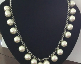 Short necklace with silver chain and all around big white pearls.