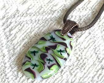 fused glass dragonfly pendant with swirls of green and burgundy brown.