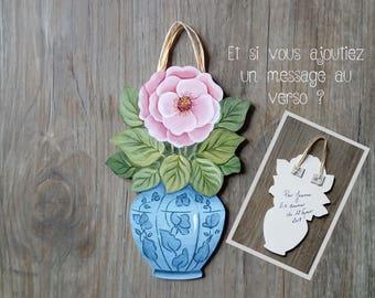 A single pink rose in a blue vase