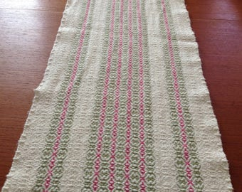 Handwoven table runner with natural, green, and coral stripes