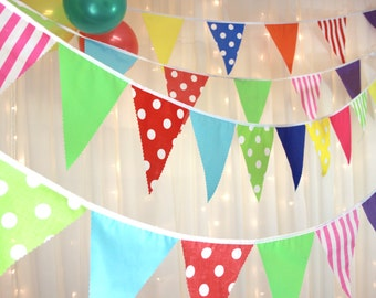 Vibrant multi coloured party bunting with spots, stripes, plains, red, yellow, green, blue, pink, orange, purple. The perfect party bunting