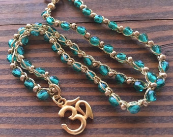 Green Crystal Beads with Gold Seed Beads and a Buddhist Pendant