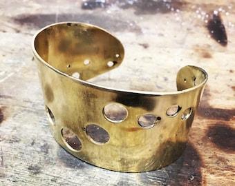 Chunky brass cuff bracelet with graduating circle cutouts