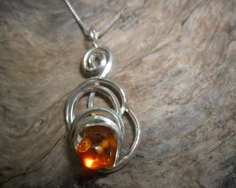 Ornate sterling silver of a bead of amber pendant