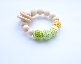 Yellow and green ring toy with crochet wooden beads. Rattle for baby.