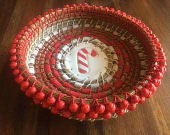 LYNN:  Pine needle basket embellished with ceramic candy cane center and red wood beads.  Original design, handmade by me