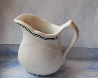 Collectible vintage 30s white porcelain creamer with curved lines and green trim. Made by Vitrified.