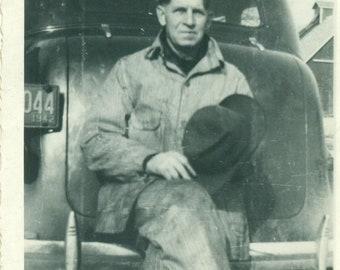 1930s Working Man Sitting on Car Bumber Holding Hat Vintage Photograph Black White Photo