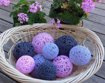 Marbled baby pink, marbled light grey, and dark grey yarn balls