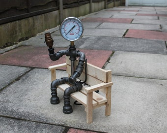 Sitting Pipe lamp made from malleable steel pipe fittings making use of a pressure gauge as the head. sat on a simple wooden bench.