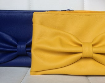 Zipped hand clutch in saffron yellow leatherette bow