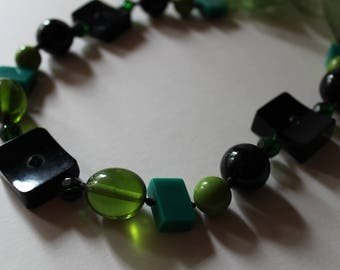Forest green lucite and glass beaded necklace.  On ribbon