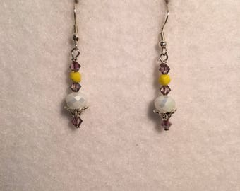 White dangle earrings with yellow and purple accents