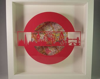 London skyline papercutting - framed with London map pages behind