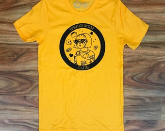 Weird Mom Club Logo on a mustard gold shirt.