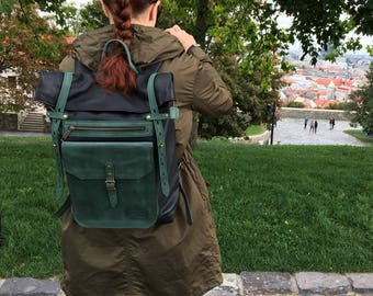 Black and green roll top leather backpack.
