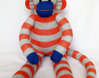 Orange and grey and blue striped Sock Monkey with blue striped pom pom hat