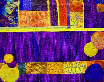 An art quilt for sale. Fiber art wall quilt in a geometric abstract style. Striking purple and gold colors.