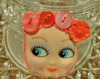 Flower Crown Frida Doll Brooch- kitsch, cute, vintage kewpie face on bright pink felt with vintage buttons and silver brooch back